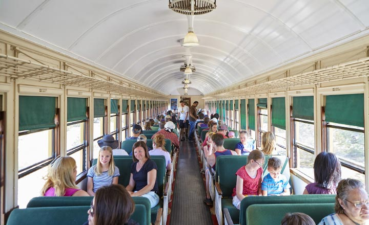 View of the Grand Canyon Railway car with visitors enjoying the view through the windows.