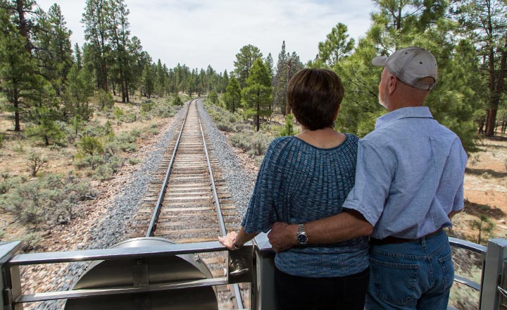 Man and woman standing on the back of the Grand Canyon Train enjoying the view behind the train car.