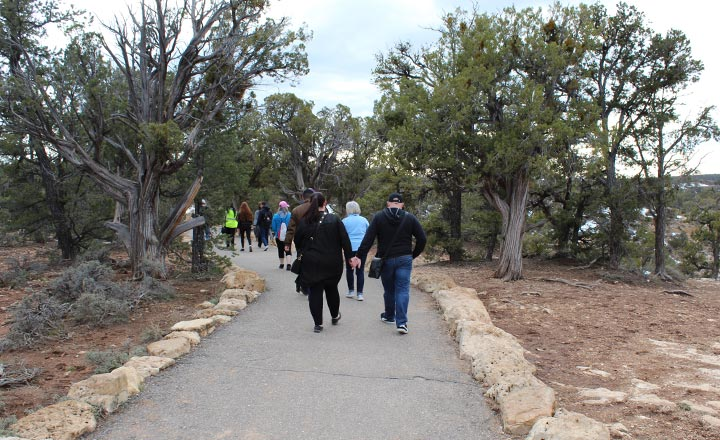 Visitors of Grand Canyon National Park walking along the paved Trail of Time at the edge of the canyon on a Grand Canyon South Rim tour.