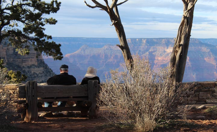 A man and woman sitting on a bench at the edge of the Grand Canyon South Rim enjoying the view during sunset.