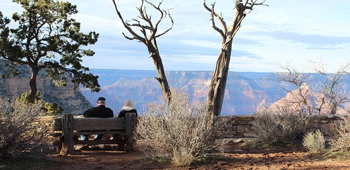Couple enjoys the view into the South Rim Grand Canyon.